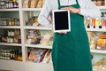 Owner showing digital tablet in store midsection of male grocery Royalty Free Stock Image