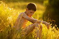 Oy sitting and relaxing in the grass on a sunset Royalty Free Stock Image