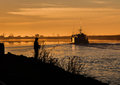 Oyster boat heading offshore and a fisherman fishing from the shoreline early morning at sunrise with man at edge of canal in Royalty Free Stock Photo