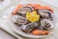 Oysters shell, jumbo shrimp with lemon on ice