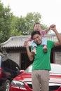 Père de sourire avec le fils sur ses épaules regardant l appareil photo dehors Photographie stock