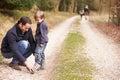 Père helping son to mis sur la chaussure pendant la promenade de famille Photo stock