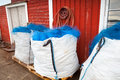 Packed blue fishing nets lay in small norwegian village Stock Photos