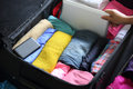 Packing for new journey clothes and digital producets into suitcase Royalty Free Stock Images