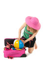 Packing the suitcase by a young woman pink for summer vacation an blond Royalty Free Stock Photo