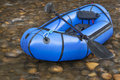 Packraft with a paddle blue pacraft one person light raft used for expedition or adventure racing kayak against shallow river Royalty Free Stock Images