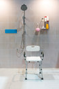 Padded shower chair with arms and back in bathroom with bright t