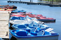 Paddle boats and kayaks attached to a dock on a sunny day Stock Photo