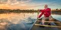 Paddling canoe at sunset senior paddler enjoying a on a calm lake riverbend ponds natural area fort collins colorado Royalty Free Stock Image