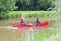 Paddling a canoe two people down quiet river in the united kingdom Royalty Free Stock Image
