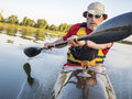 Paddling a fast kayak senior male is racing sea with wing paddle on calm lake fort collins colorado Stock Images