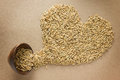 Paddy in heart shape on brown background and bowl Royalty Free Stock Photos