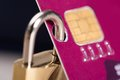 Padlock attached to credit card closeup of against black background Royalty Free Stock Photo
