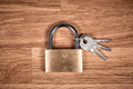 Padlock and keys on a brown wooden table Royalty Free Stock Photo
