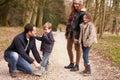 Padre helping son to puesto en el zapato durante paseo de la familia Imagen de archivo libre de regalías