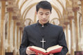 Padre looking down na bíblia em uma igreja Imagens de Stock Royalty Free