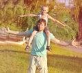 Padre man della famiglia e ragazzo del figlio che si siede sul gioco delle spalle all aperto Fotografia Stock