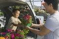 Padre passing flower pot al hijo en la parte de atrás de un minivan Foto de archivo libre de regalías