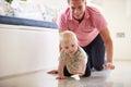 Padre and young son che striscia insieme intorno alla stanza Fotografie Stock