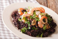 Paella from black rice with seafood close-up on a plate. horizon Royalty Free Stock Photo