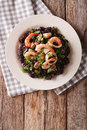 Paella from black rice with seafood close-up on a plate. Vertica Royalty Free Stock Photo