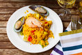 Paella served in white plate on wooden table traditional spanish dish Royalty Free Stock Image