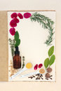Pagan love potion ingredients over natural hemp notebook and mottled cream paper background Stock Photography