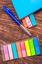 Page markers multi coloured on a table with a pen and a book of which three pages has already been marked Royalty Free Stock Photo