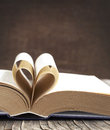 Pages of a book curved into a heart shape on wooden background Stock Image