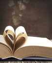 Pages of a book curved into a heart shape on wooden background Royalty Free Stock Image