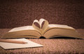 Pages of open book rolled in heart shape on table Royalty Free Stock Photo