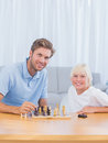 Pai de sorriso que joga a xadrez com seu filho Fotografia de Stock