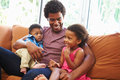 Pai relaxing on sofa with young children Imagens de Stock