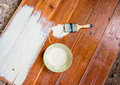Paint brush and bowl of white coating color put on wood board top view with Royalty Free Stock Photography
