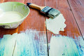 Paint brush and bowl of white coating color put on wood board top view with Stock Photo