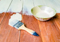 Paint brush and bowl of white coating color put on wood board top view with Royalty Free Stock Image