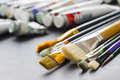 Paint brushes on the background of tubes of paint Royalty Free Stock Photo