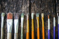 Paint brushes of different sizes have different colors in a row horizontally on an old wooden table Stock Images