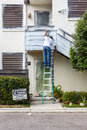 Paint contractor on low ladder applying by hand Stock Photo