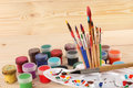 Paint palette, dirty brushes and gouache on wooden background Royalty Free Stock Photo