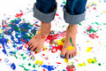 Paint splash feet a young girl s covered in colorful on a splashed background she has her jeans rolled up to avoid the mess Royalty Free Stock Photo