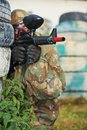 Paintball player adrenalin in protective uniform and mask aiming gun before shooting in summer Stock Image