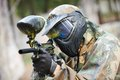 Paintball player in protective uniform and mask aiming gun before shooting in summer Royalty Free Stock Photography