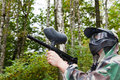 Paintball player shoots aside in forest Royalty Free Stock Images