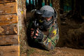 Paintball players hide behind tree sport player in protective uniform and mask aiming and shooting with gun outdoors Royalty Free Stock Image