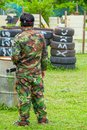 Paintball sport player in protective uniform and mask playing wi Royalty Free Stock Photo