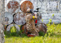 Paintball sportsman in ambush behind rusty barrels outdoors Stock Photography