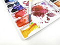 Paintbrush on art palette with blobs Royalty Free Stock Photo