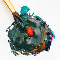 Paintbrush blends multicolored watercolors paints and red gouache drop close up Royalty Free Stock Photo