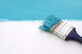 Paintbrush with blue paint, painting over white board Royalty Free Stock Photo